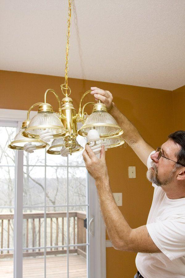 Home owner install energy saving light bulbs in dinin Energy saving light bulbs Home owner install energy saving light bulbs in dinin saving light bulbs Home owner instal...