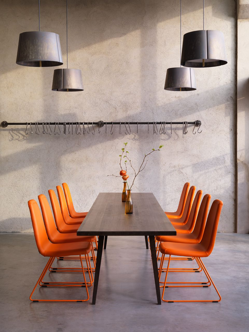 Game meeting chair in pure solid orange colour against dark wood and pale grey room surfaces
