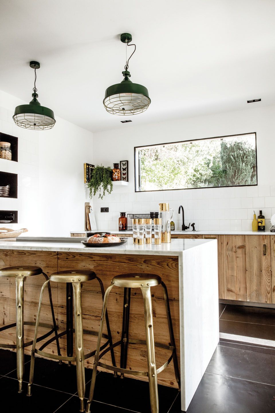 Wooden kitchen with brass metal bar chairs and green hanging