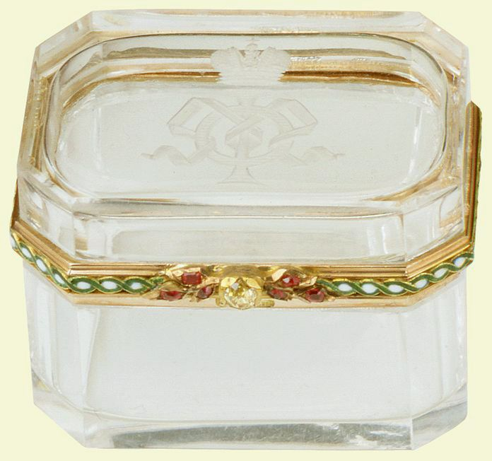 Fabergé rectangular straight sided box with canted corners of rock crystal, lid engraved on underside with Tsarina's crowned AA monogram, hinged gold rim mounts on three sides with green and white guilloché enamel border and faceted topaz and ruby thumb-piece. The cypher engraved on this box indicates that it belonged to Tsarina Alexandra Feodorovna. Mark of Michael Perchin.
