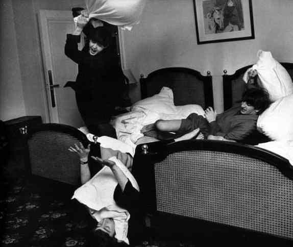 Beatles in Paris hotel room in the midst of a pillow fight, photo session. Paul whacking John (on the floor) with a pillow.