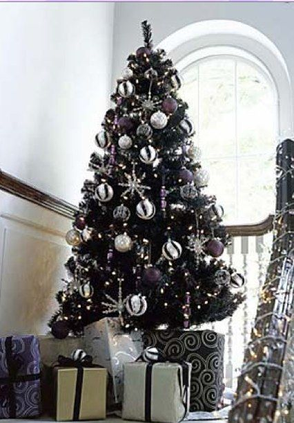 black christmas tree with white gray silver and black ornaments