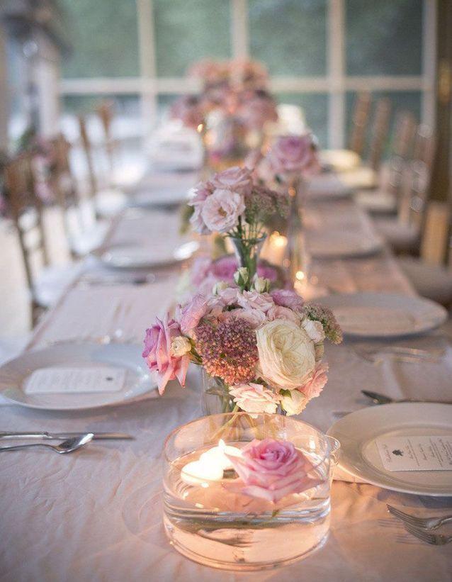 meler bougies et fleurs flottantes sur la table de mariage