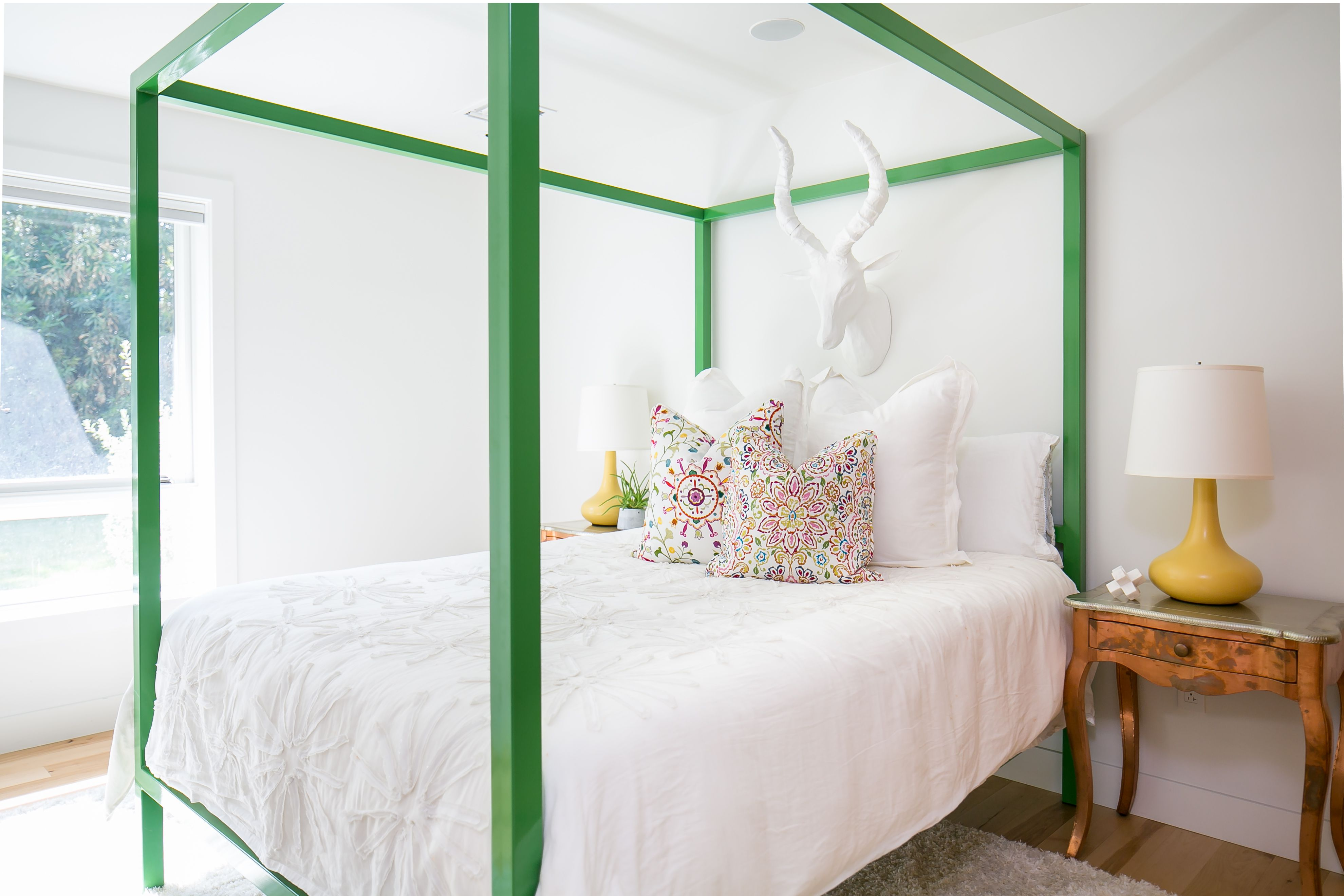 Minimalist Guest Room With Fun Accents Yellow Table Lamps Green Bed Frame And Ceramic Animal Head Wall D With Images Green Bedding Interior Design Firms Interior Design