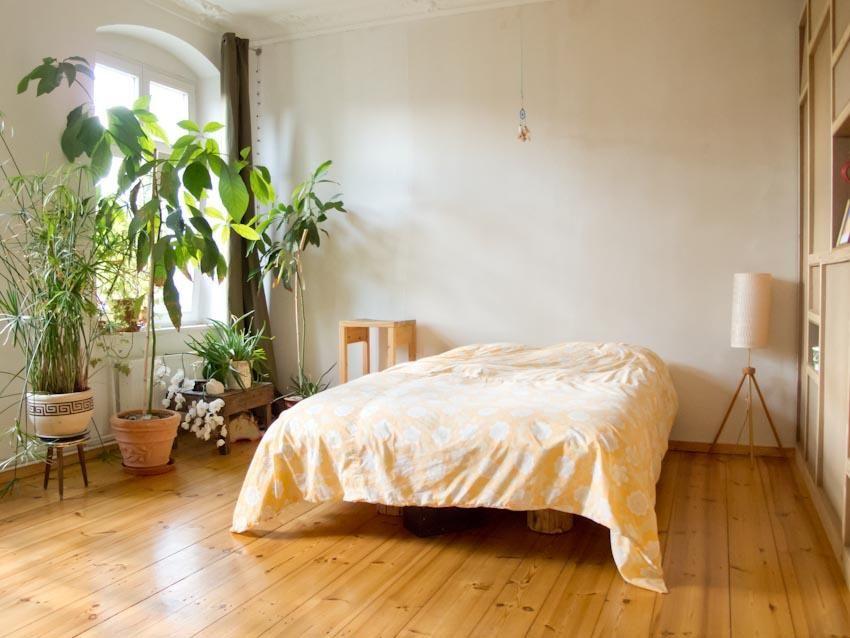 Minimalistische Schlafzimmer Einrichtung Mit Vielen Grünen Pflanzen,  Parkettboden Und Hohem Altbaufenster. 2