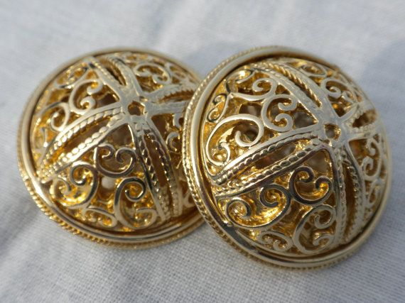 These large 1980s gold tone domed openwork clip on earrings feature a stylized cross (or flower) with scrollwork and beading. These are a