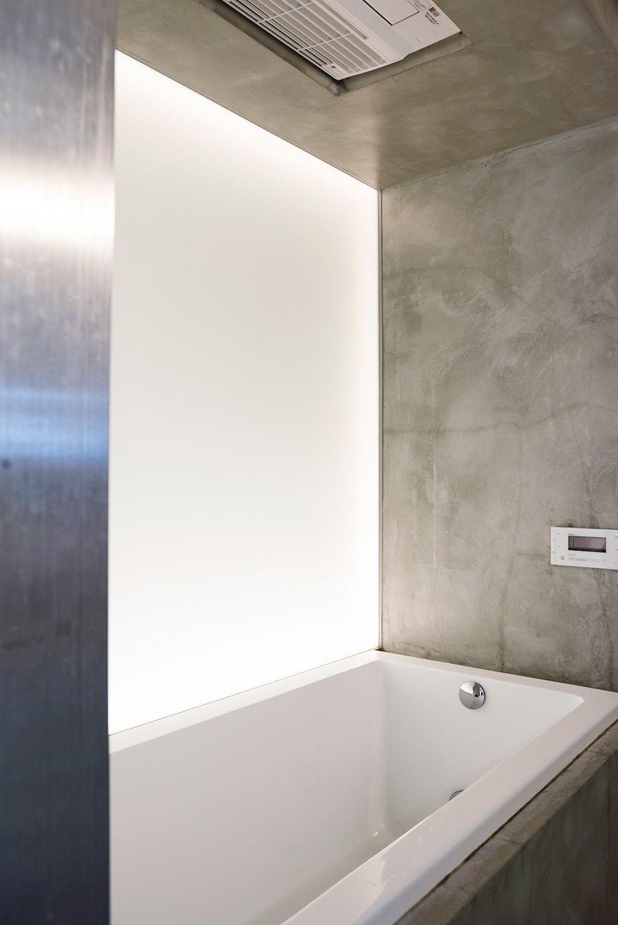 モルタルのモダンでクリーンなバスルーム 配管のあった壁側は内照式の