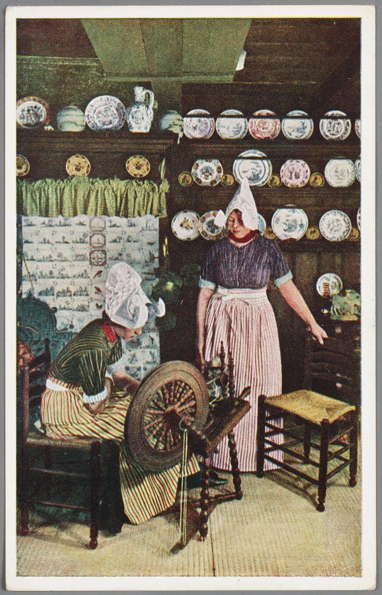 Twee vrouwen in dracht in een interieur te Volendam met spinnewiel ...