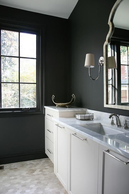 Black and white bathroom features a black wall lined with ...