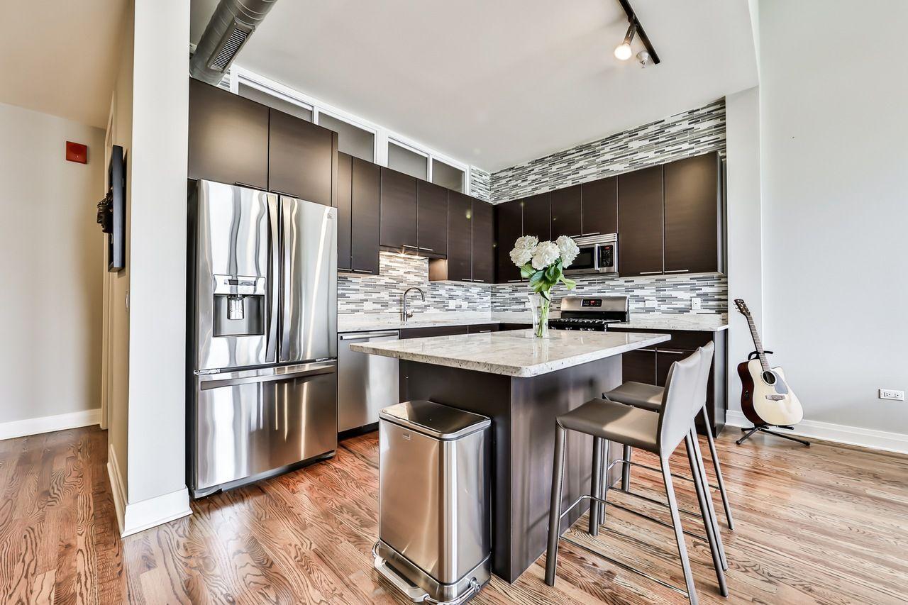 Modern kitchen with hardwood floors, stainless steel