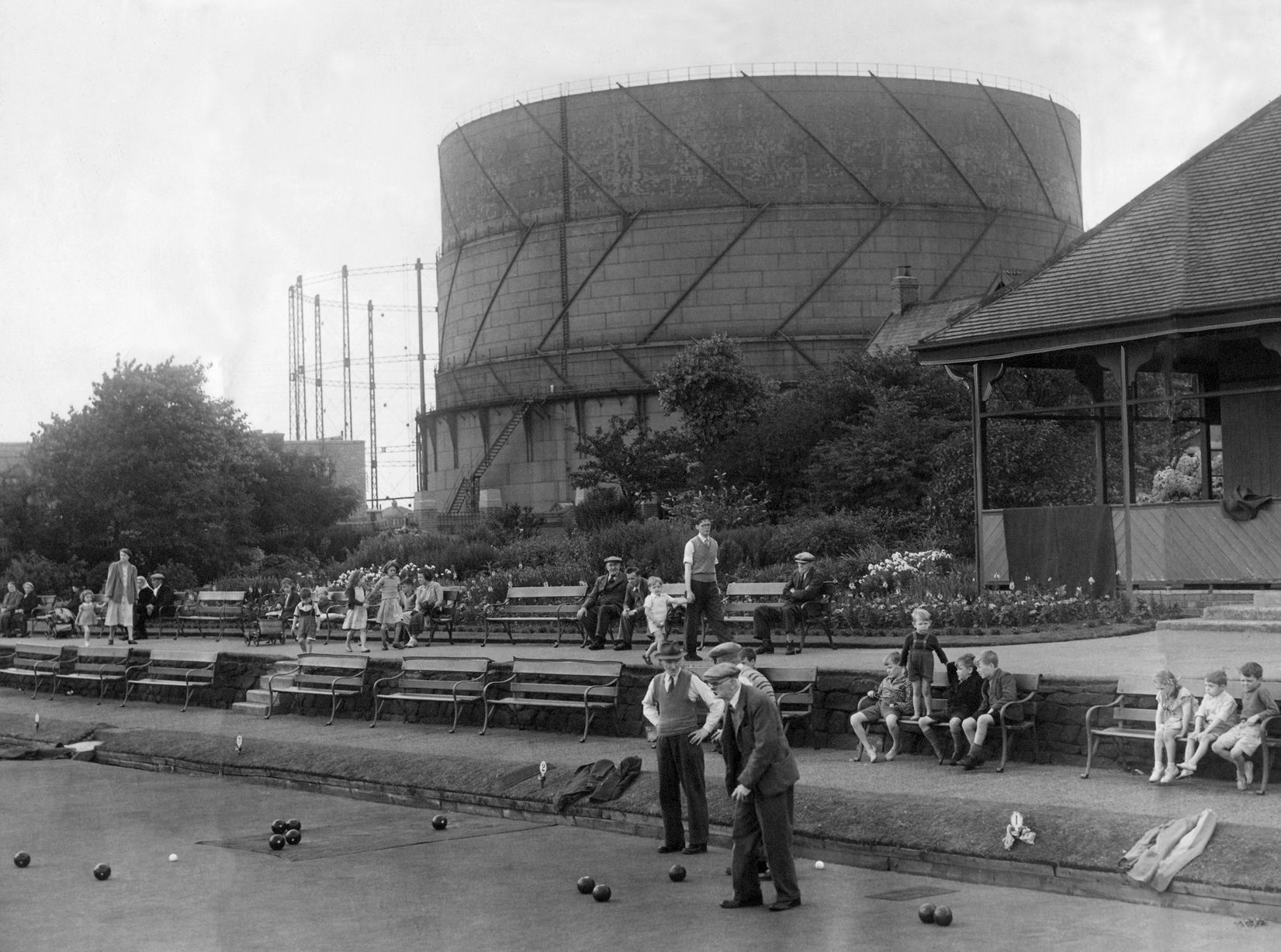 A summer scene at Howdon Park with men playing bowls and children looking on. But behind them, the gas holder rears up like a monstrous monument to an age of ugliness