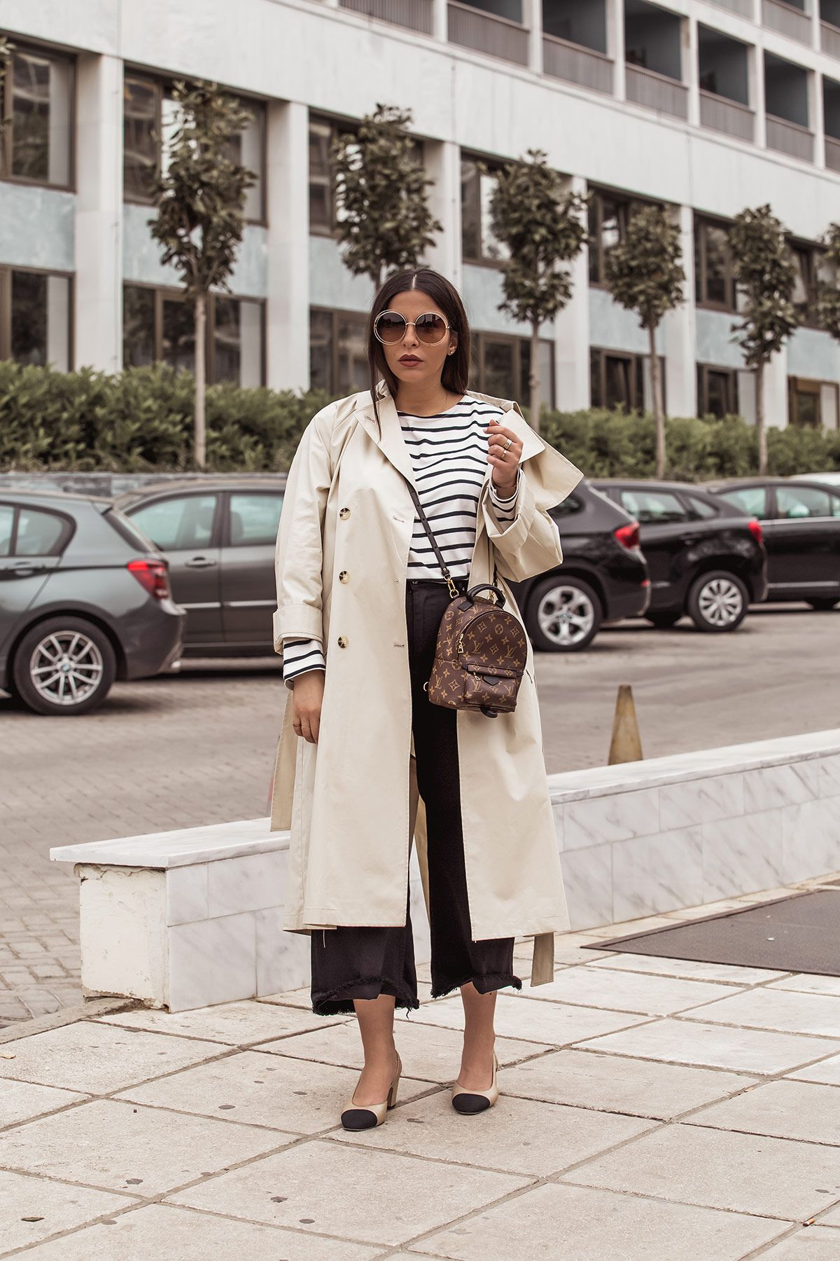 c5a1a5ca36 ... beige trench coat, breton top, Louis Vuitton Palm Springs backpack as a  cross body, black denim culottes, Chanel slingbacks and Chloe Carlina  sunglasses