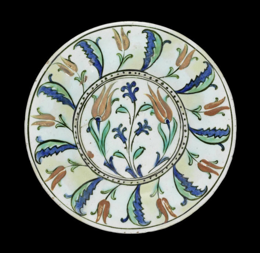 An unusual Iznik pottery Dish Turkey, late 16th Century with wide sloping rim, decorated in polychrome and gilt, the centre with a hyacinth spray flanked by tulips, the rim with a frieze of tulips alternating with saz leaves 25.5 cm. diam.