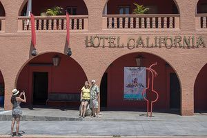 Tourists Pose For A Photograph Outside Hotel California In Todos Santos Baja