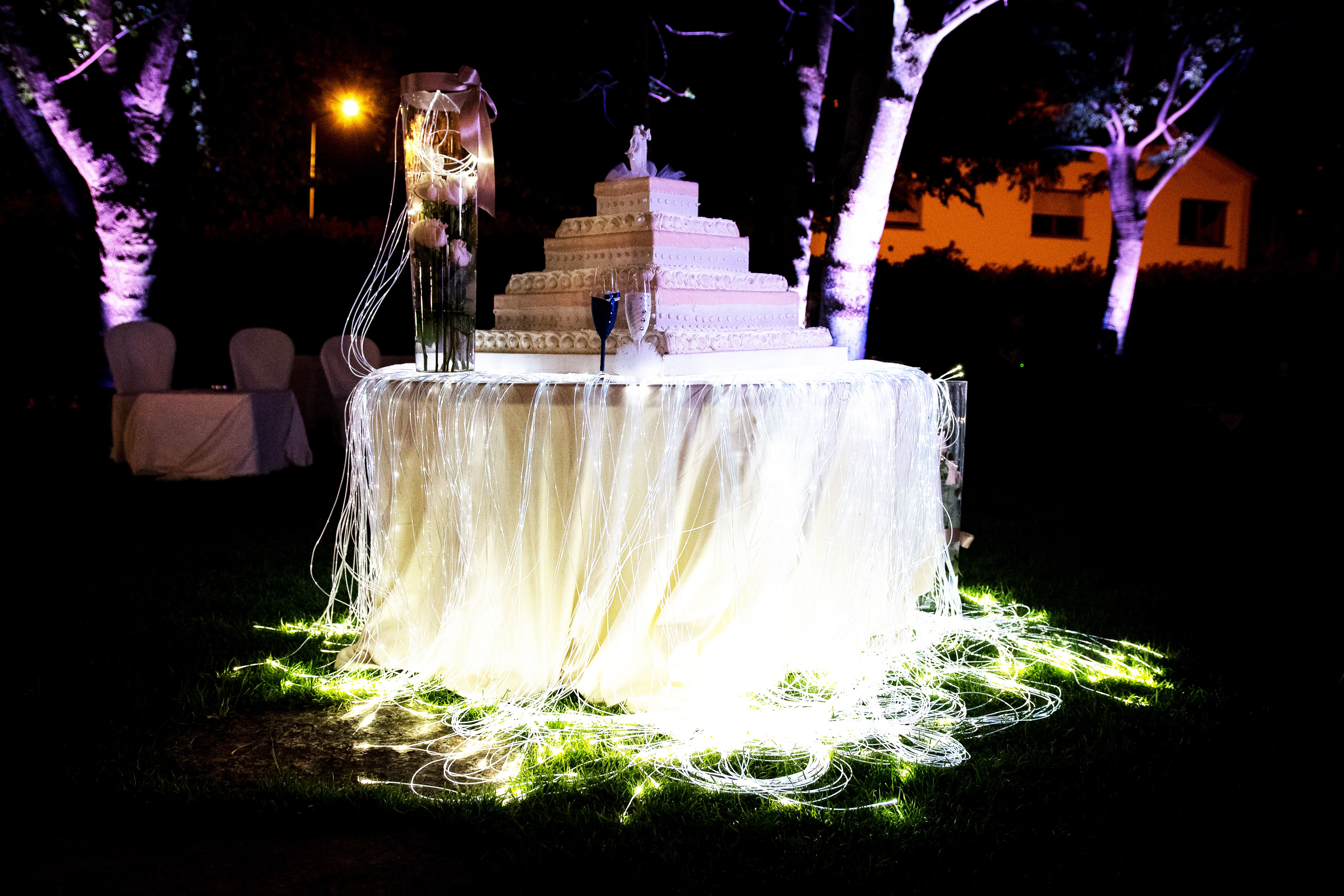 Tavolo con torta nuziale e fibre ottiche attorno illuminazione