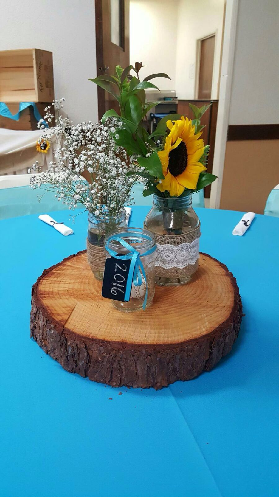 Sunflower mason jar centerpieces on wood slab graduation