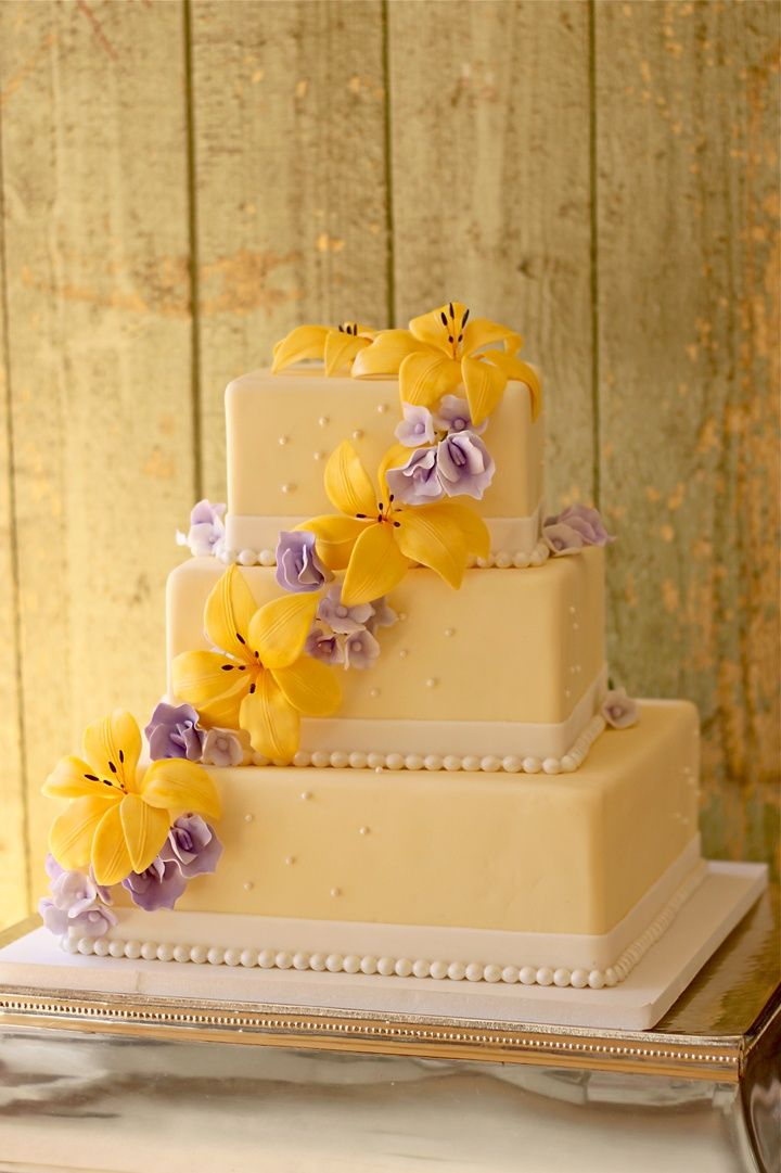 Yellow and purple square layered wedding cake with cascading fondant ...
