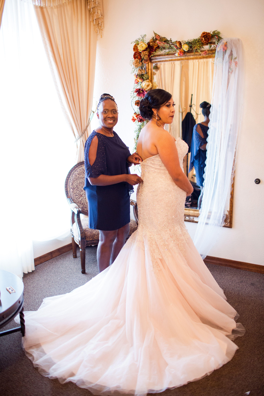 d9f7d908d9 Bride s mother helping her zip up her bridal dress