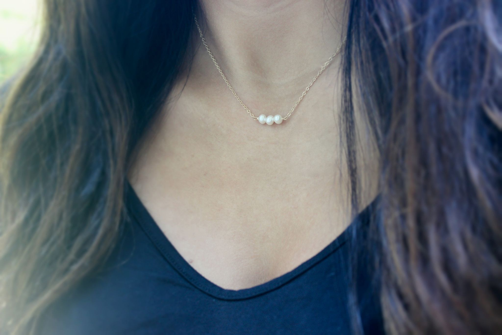 A simple gold necklace featuring three freshwater pearls suspended from a 14K gold fill chain. The necklace features a springring clasp. All metal components are 14K gold fill. The perfect necklace th