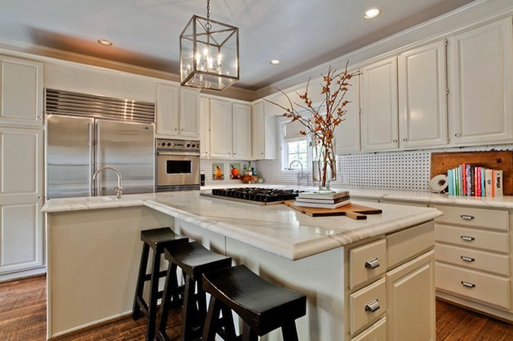 Fantastic kitchen with off-white cabinets paired with calcutta gold marble countertops and black an d white backsplash.