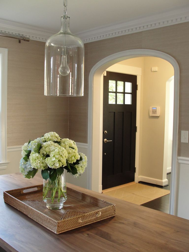 White Interior Front Door dining grasscloth wallpaper and arch moulding + black door +