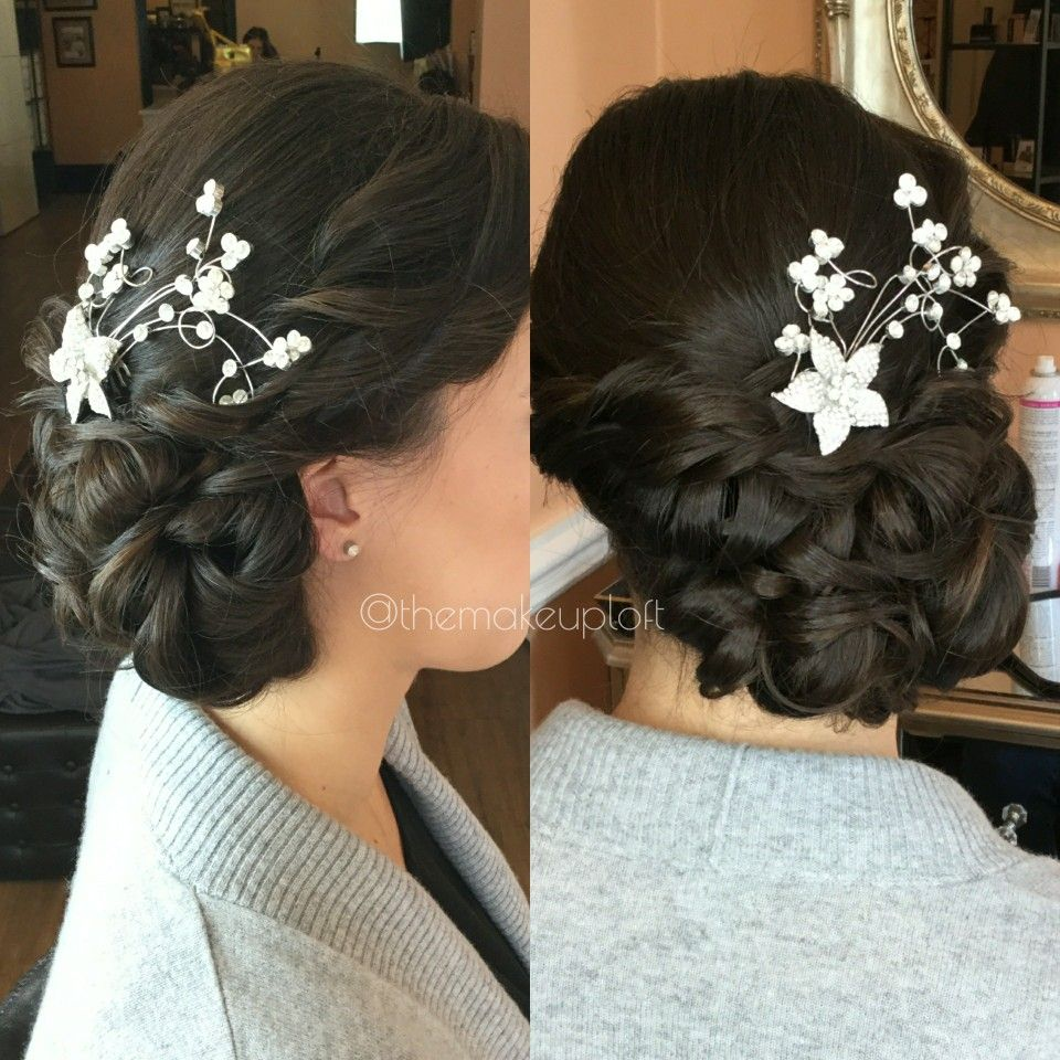 side curly updo formal hairstyle with floral hair piece   brunette