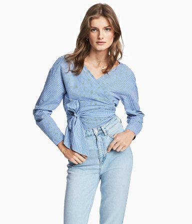 Blå/Hvidternet. Langærmet bluse i let, vævet bomuldskvalitet. Blusen er i slå om-facon foran med bredt bindebånd i siden.