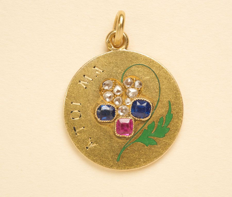 """An 18 carat gold love token with the text """"A toi ma pensée"""" (I think of you), where the word """"penseé"""" has been replaced by a pansy set with rose cut diamonds, two sapphires, a ruby and a stem of green enamel. The name """"pansy"""" is derived from the French word pensée meaning """"thought"""", France, circa 1900."""