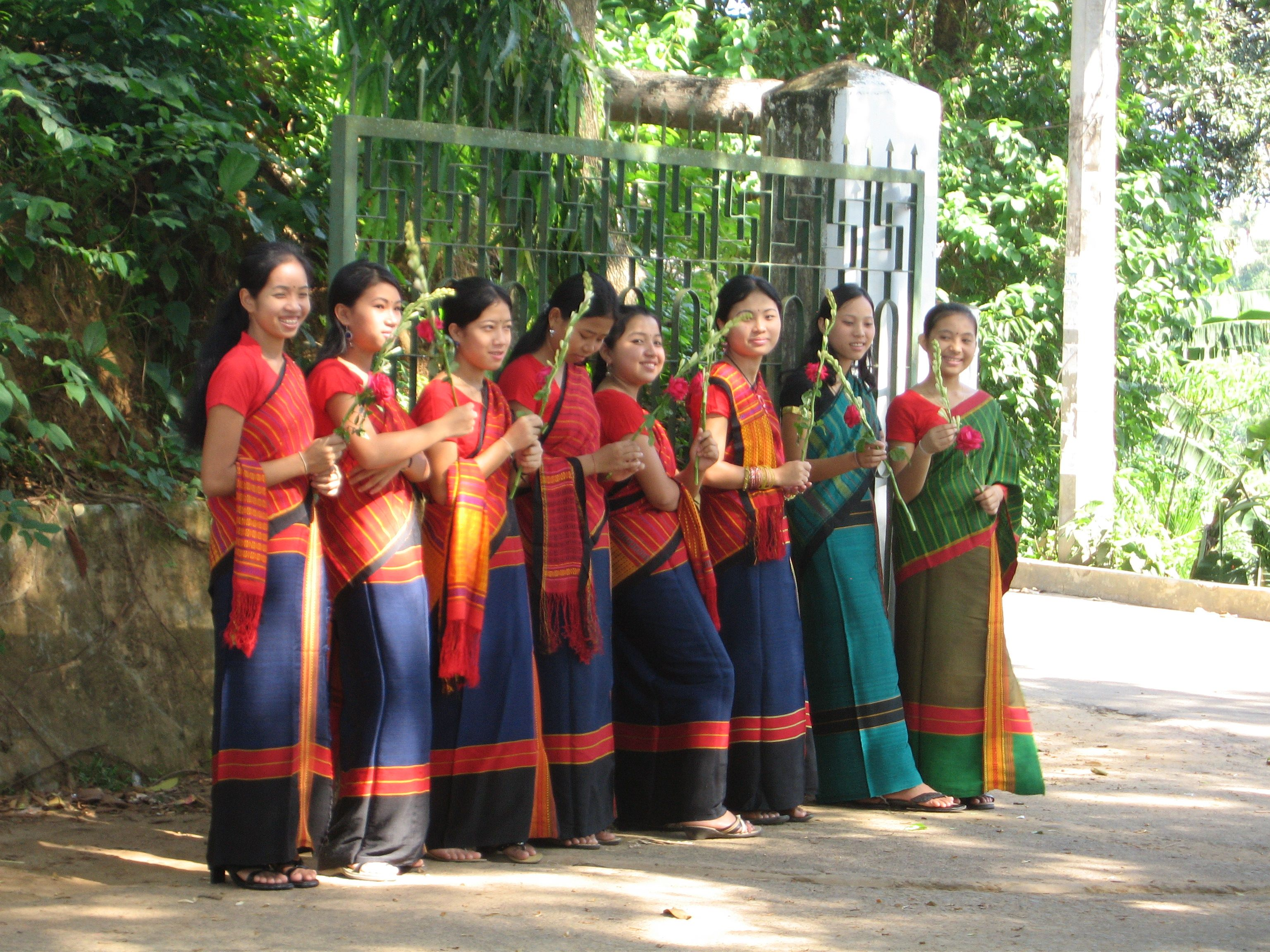 Schoolgirls in Chakma dress ready to welcome guests.  The Chakmas are a community that inhabits North-East India.  Chakmas are divided into 46 clans or Gozas. Chakmas have their own language, customs and culture, and profess religion, Theravada Buddhism.  Chakmas are Tibeto-Burman, and are thus closely related to tribes in the foothills of the Himalayas.