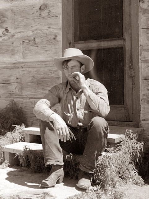 Cowboy by Bunkhouse - photo taken in the 1930s at the Quarter Circle U Ranch in Big Horn County, Montana.  He would have rolled his own cigarette ~ you can see the pouch of tobacco in his right shirt pocket