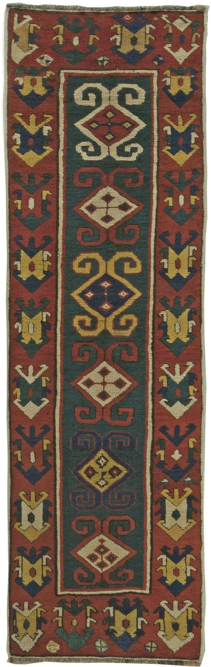 This unique circa-1890 antique Caucasian runner rug features an all-over design of bold geometric abstractions in shades of red, blue and yellow against a field of green. The thick red border framing the central pattern almost dominates it in size and use of similar geometric motifs, highlighting an innovative approach to conventional textile design structure. The Caucasus are a primarily mountainous region in Southern Russia bordered by the Caspian Sea and the Black Sea. Transcaucasia, an…