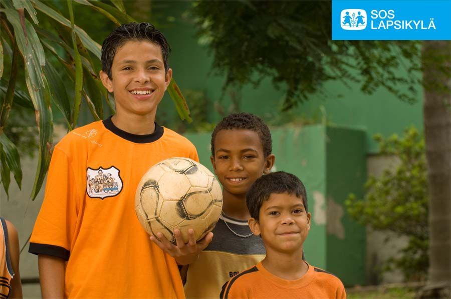 SOS-lapsikyläperheen veljekset poseeraamassa pallon kanssa Kolumbiassa. Pelaamisen into loistaa poikien kasvoilta. #jalkapallo #SOS-Lapsikylä #Kolumbia