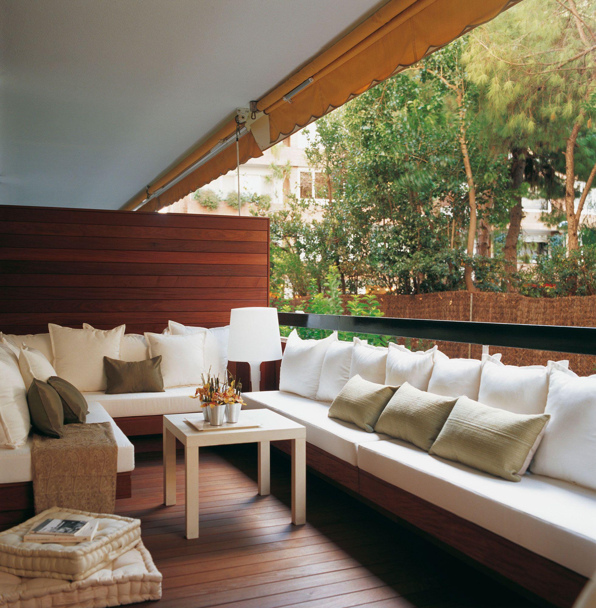 Terraza urbana con pavimento de madera y sof s blancos for Terrazas con sofas