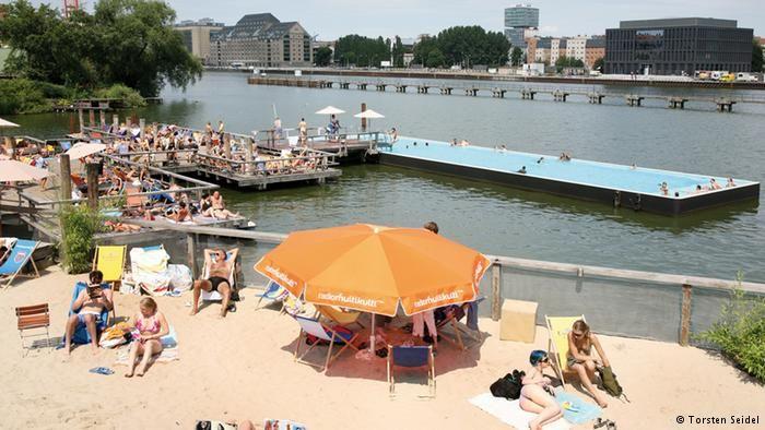 Urban Beaches - Berlin, Germany - Badeschiff Berlin  Im Hintergrund schwimmt das Badeschiff auf der Spree. Vorne entspannen Menschen auf dem Sandstrand.