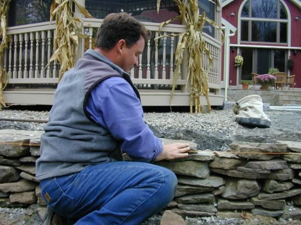 Begin building the wall by setting corner stones (those with a 90-degree corner) at either end of the wall and on both sides of the granite steps. Start setting face stones (those with a flat face) between the corner stones. Every three or four feet, lay a tie-back stone (flat, long and heavy) to provide additional stability. Continue laying corner and face stones to build up the wall until desired height is almost reached. Regularly check that the wall is plumb. For the final course use cap…