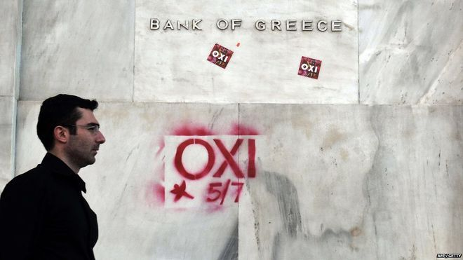 "A pedestrian walks past the bank of Greece with ""NO"" signs referring to the upcoming referendum in Athens, 2 July, 2015."
