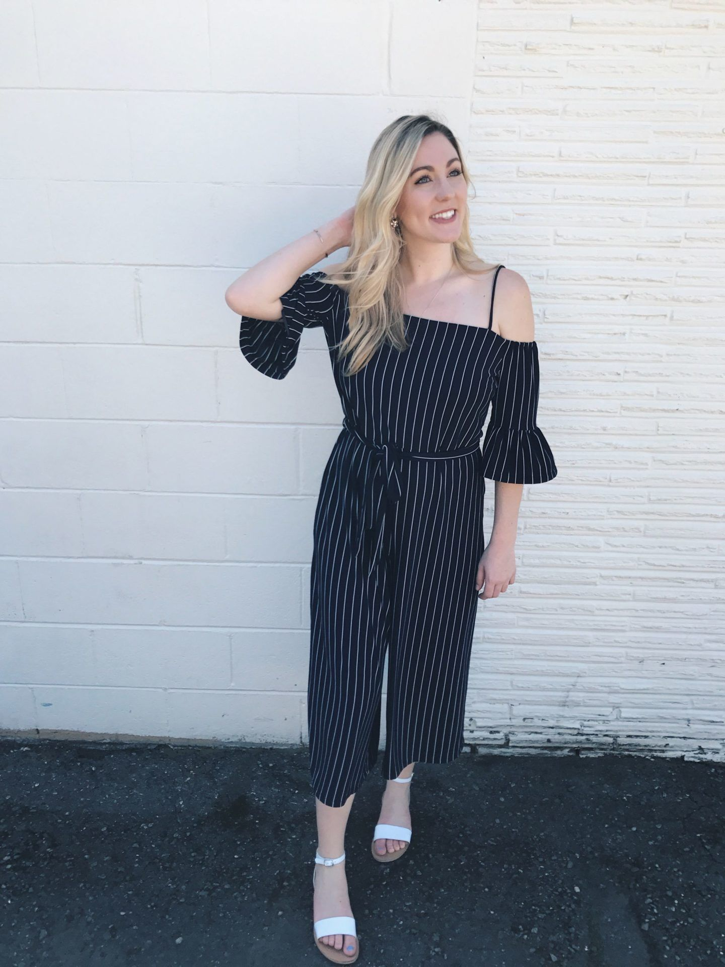 86759937bc3 Stylish woman walks in off the shoulder striped navy blue jumpsuit from  Banana Republic against white wall
