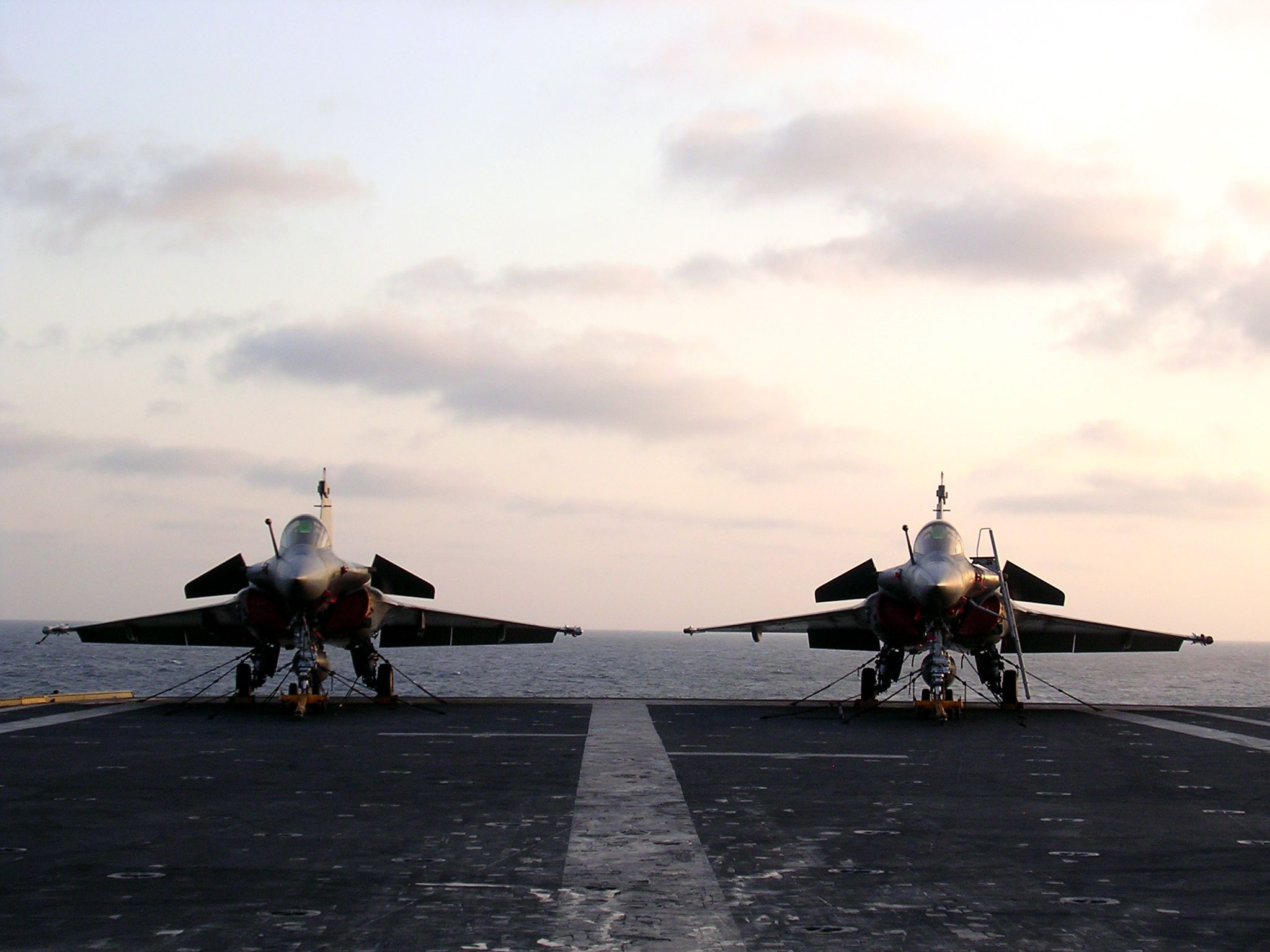 Two Rafales on the French Charles de Gaule aircraft carrier under the morning sun