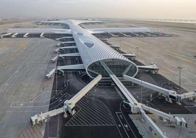 """NUEVA TERMINAL DEL AEROPUERTO INTERNACIONAL DE SHENZHEN BAO'AN, CHINA (NUEVA TERMINAL ABIERTO DE 2013) Cubierta con un patrón de panal de abeja y la friolera de 1,5 kilómetros de largo, la nueva terminal del aeropuerto de Shenzhen Bao'an fue diseñada, según comentan sus creadores del Estudio Fuksas, para evocar la forma de una pez manta. Sus arquitectos la describen como """"un pez que respira y cambia su propia forma, sufre variaciones y se convierte en un pájaro para celebrar la emoción..."""
