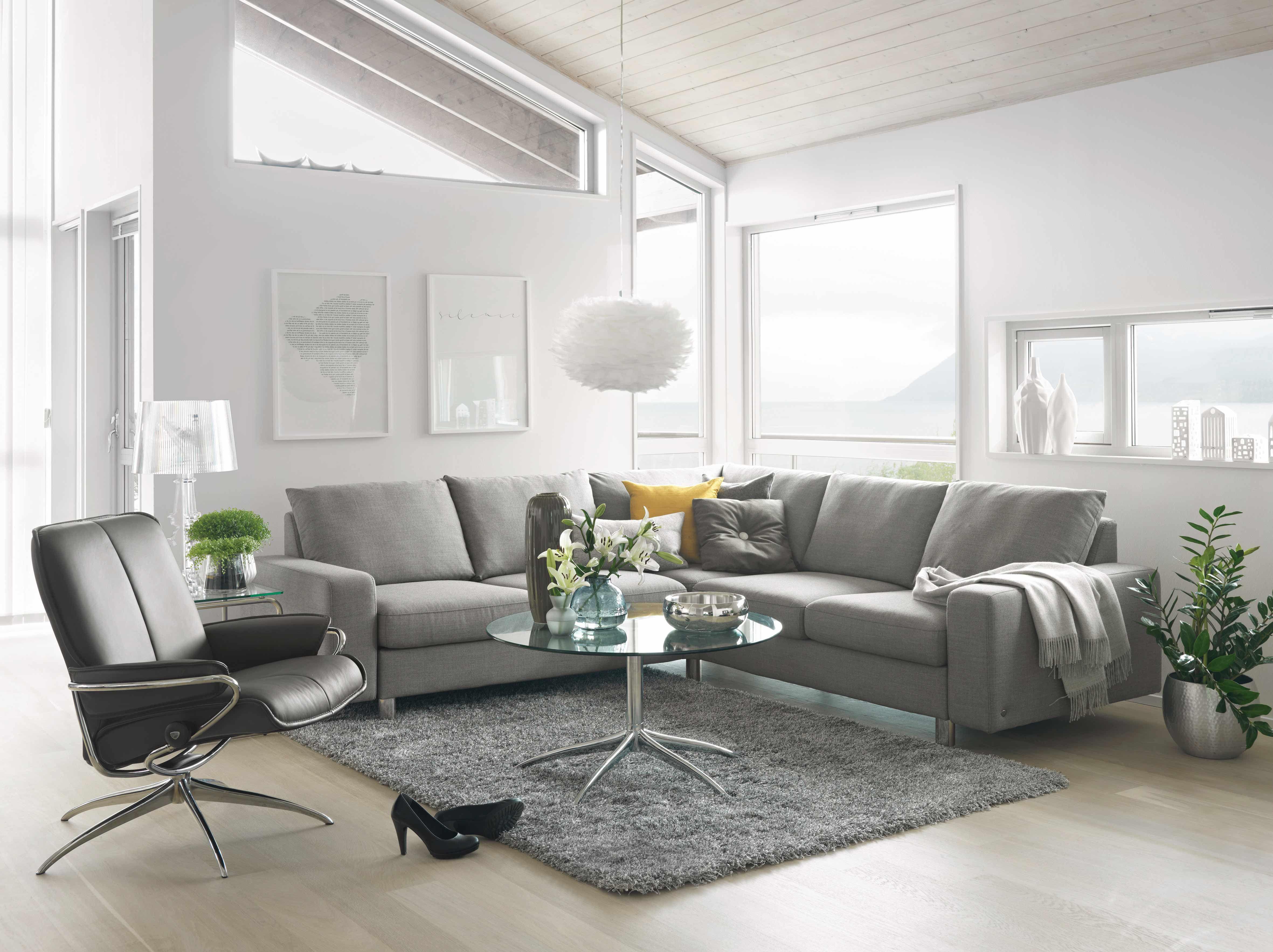 Musta tuoli ja vaalea  sohva, harmaa matto