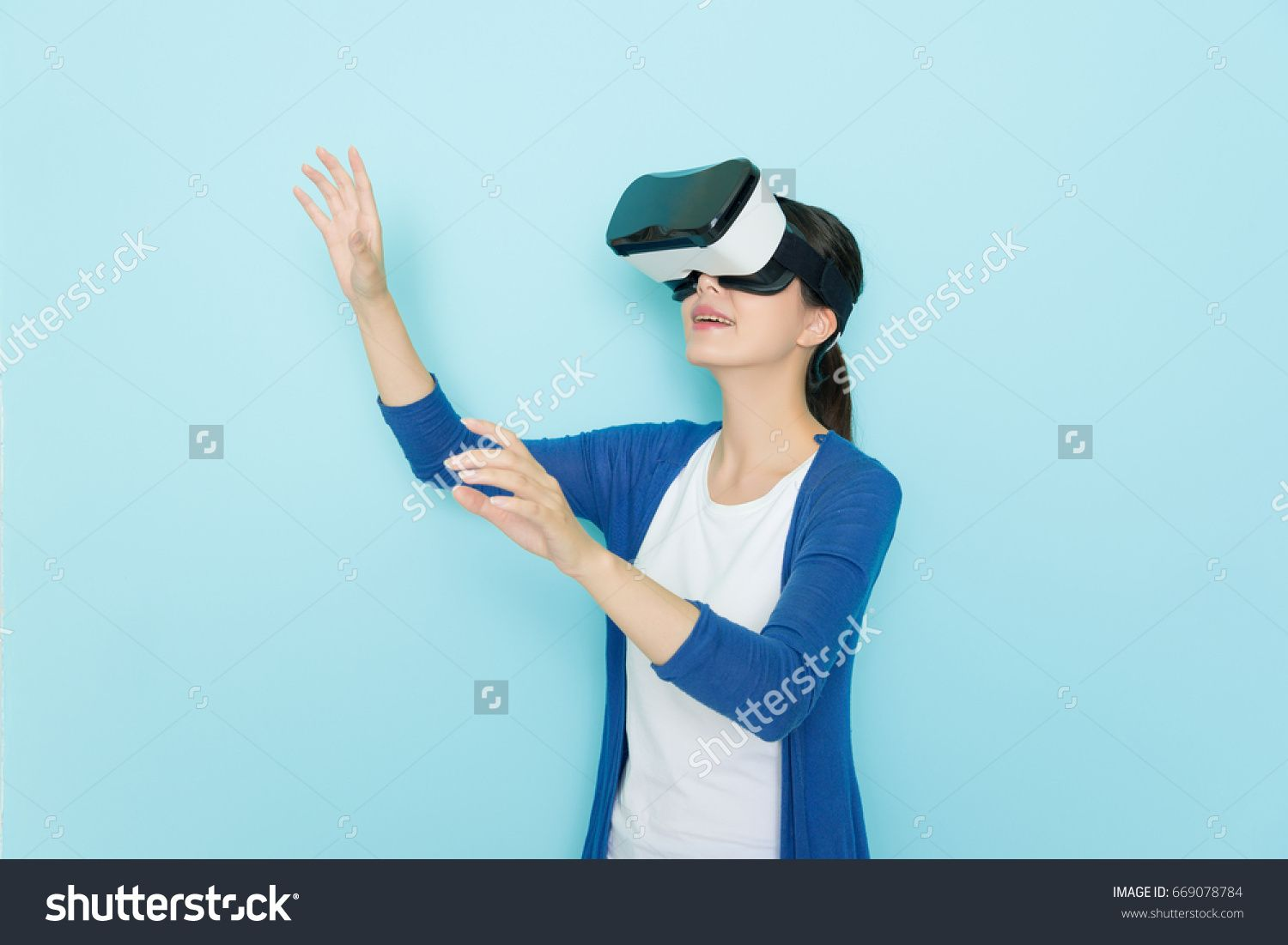 6a06c916eb smiling young woman in virtual reality glasses standing in blue wall  background and wearing lifestyle clothing using hands playing 3D online  game.
