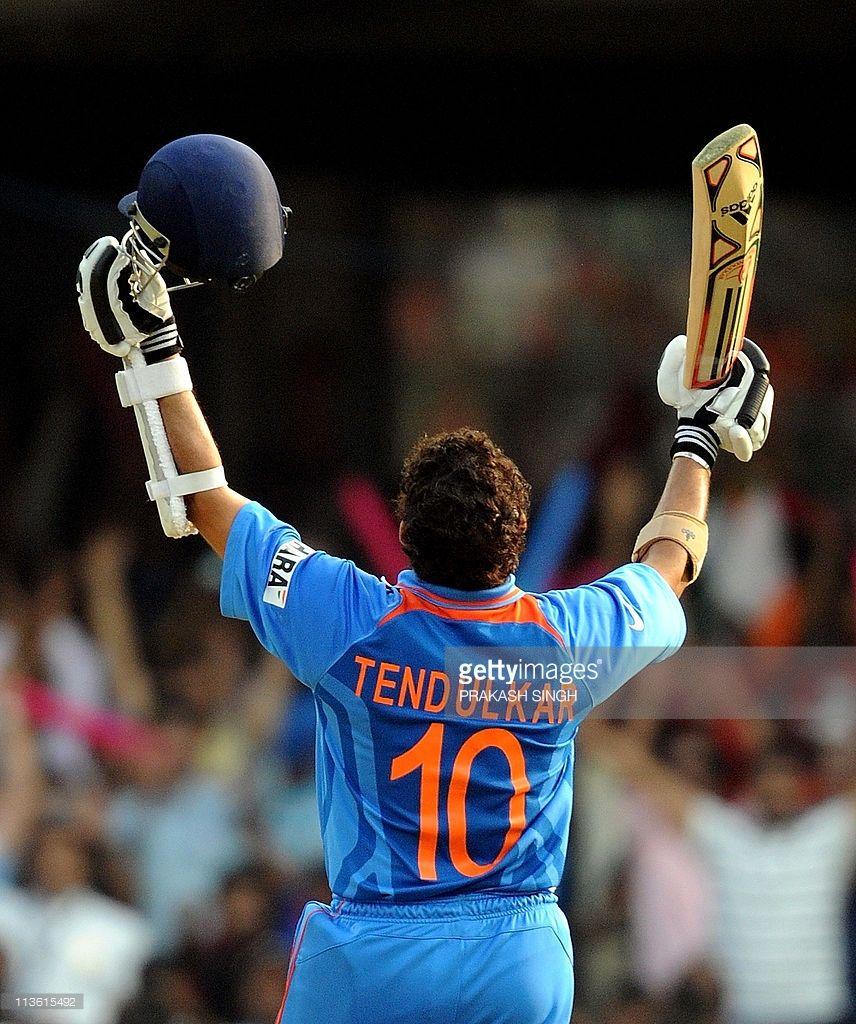 India cricketer Sachin Tendulkar raises his bat to ...