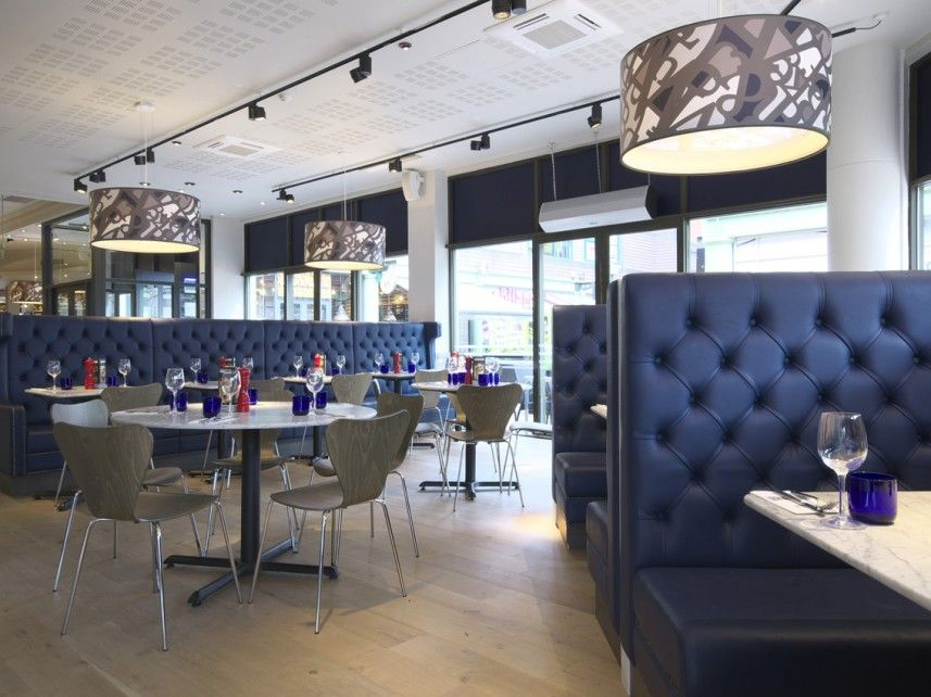 Pizza Express Birmingham Brindley Place Plush indigo banquette seating prevents the restrained colour palette from seeming clinical.