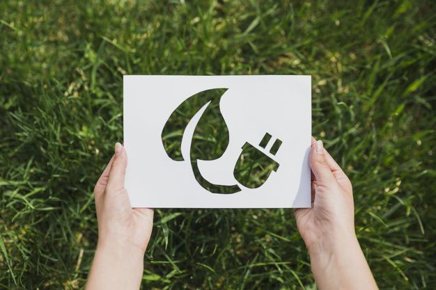 Eco concept with hands holding cut out paper showing eco energy   Premium Photo