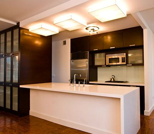 White Ceasarstone countertops, rift cut oak cabinets and a single glass panel for the backsplash.  http://newyorkartistic.com