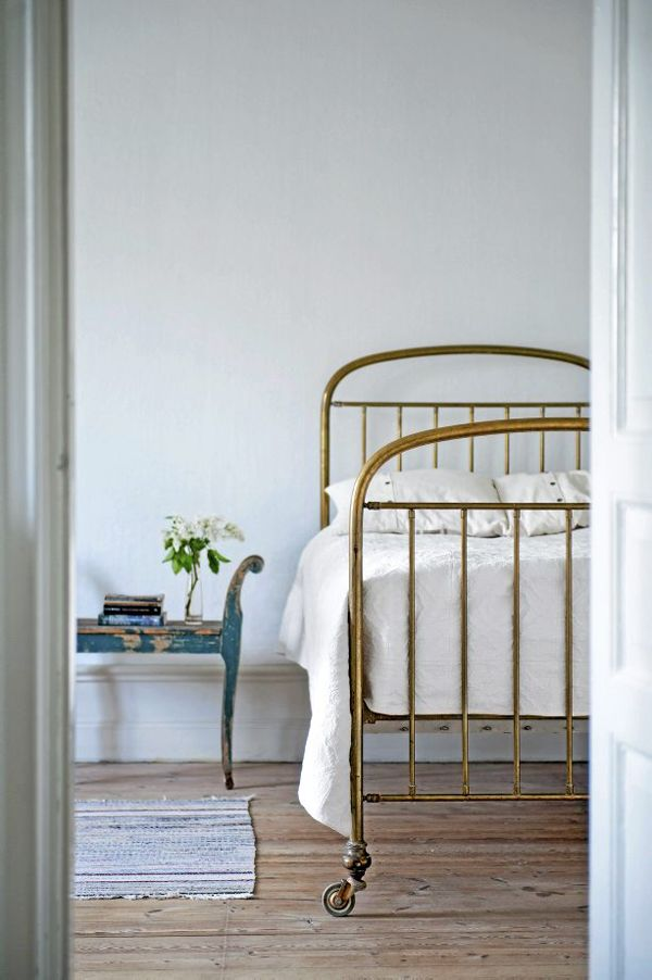 Simple bedroom. The different materials (brass, distressed wood, linen...) really make this space.
