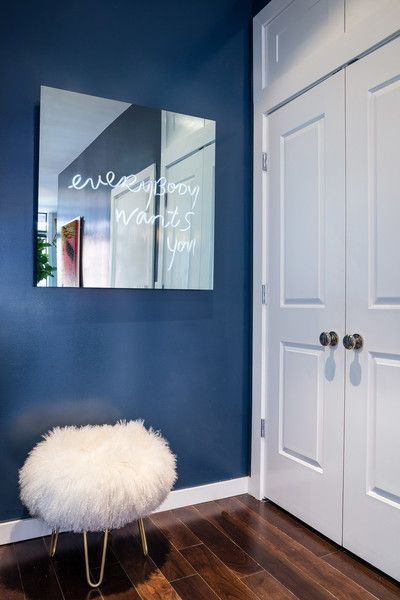 Contemporary Wall Treatment: A blue accent wall with a furry pouf and a mirror. .