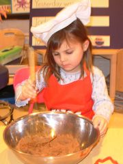 girl stirring brownie mix in a large mixing bowl