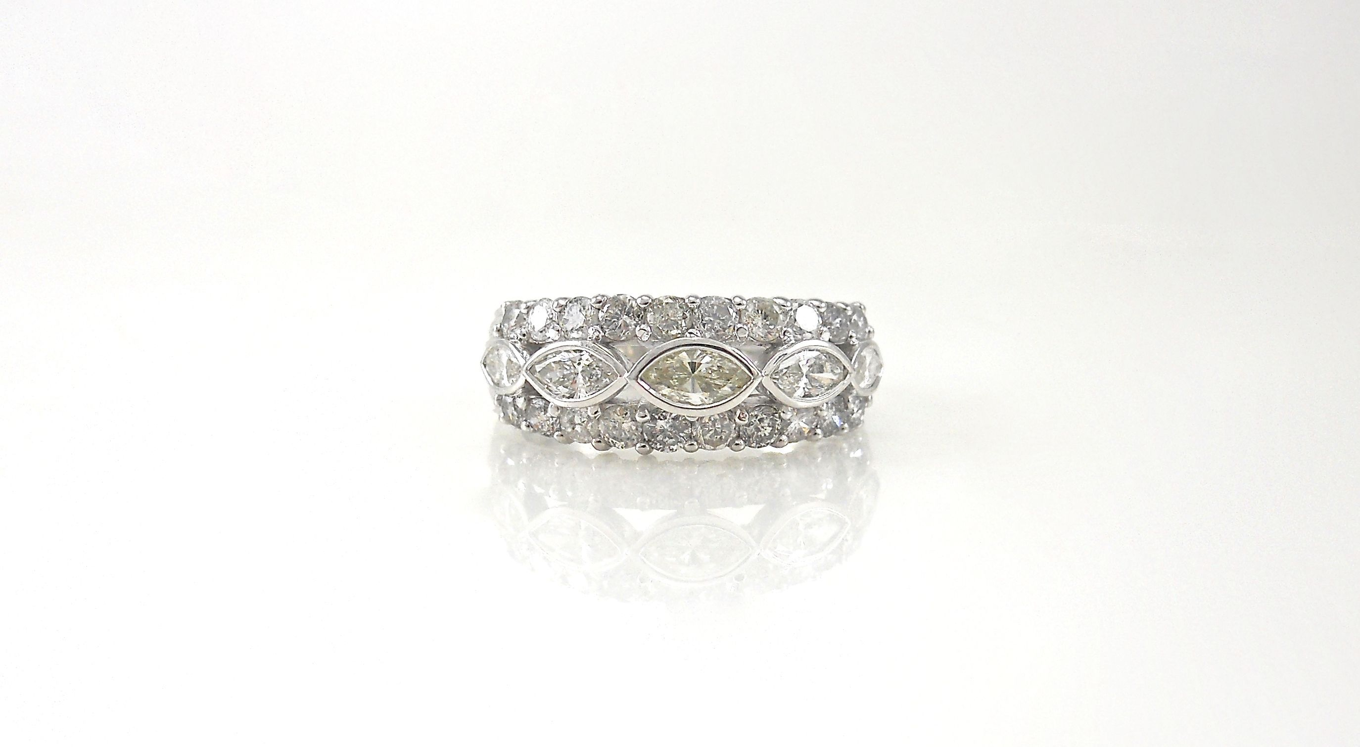 A stunning ring featuring a tailored design with a straight row of marquise diamonds at the center.