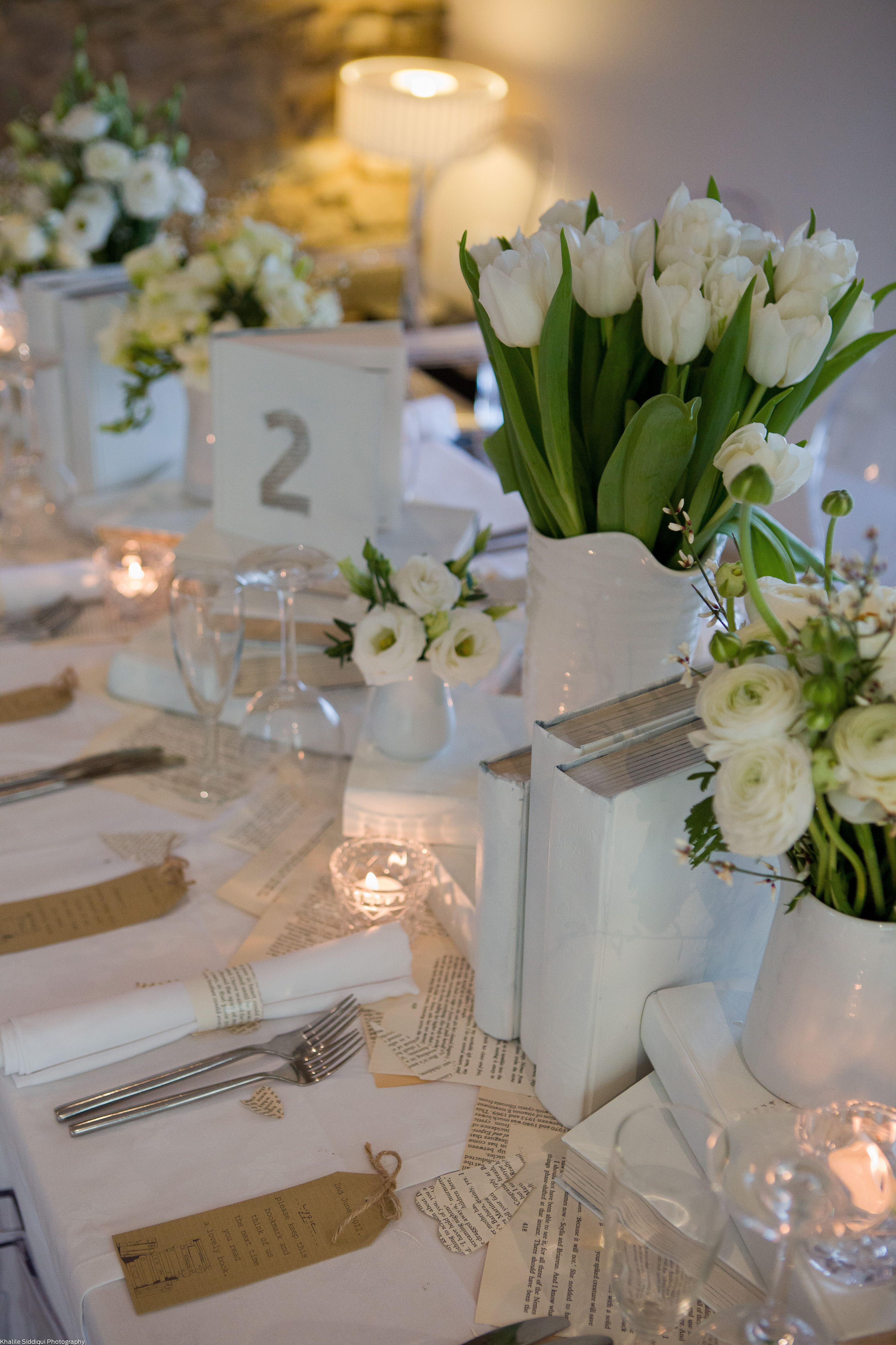 White Flowers In Small Containers Of Different Hights Along Table